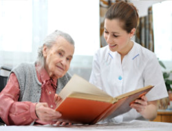 Elder and nurse reading book